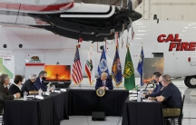USPresident DonaldTrumpsits in front of a CALFIREfirefighting aircraft as California Governor Gavin Newsom speaks during a briefing on wildfires in McClellan Park, Calif., Sept.14, 2020.