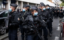 A group of police officers are shown carrying large weapons and wearing face masks while walking down the middle of a street.