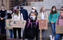 Swedish climate change activist Greta Thunberg is shown standing among a group of activists and wearing a purple backpack and a face mask.
