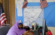 A Somali woman wearing a purple headscarf answers the phone in an office with American flags and East Africa map on the wall.