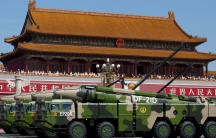 Military tanks pass by a building featuring traditional Chinese architecture.
