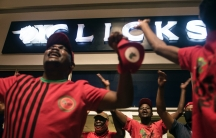 Men and women wearing red political shirts chant in front of a department store in South Africa
