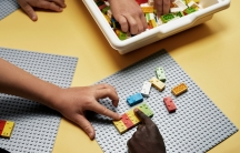 Children play with Braille Bricks on the floor as a way to learn Braille and have fun.