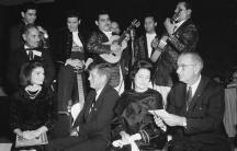 Foto en Blanco y negro del Presidente Kennedy y su esposa rodeados de musicos.