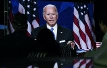 Joe Biden aparece en una pantalla mientras unas personas miran.