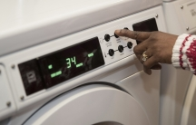 Hand reaching forward to set the timer on a washing machine