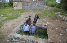 Four men are shown standing in an dug out area lined with stone in an open area near a house.