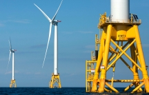 Three wind mills powered on yellow platforms in the ocean.
