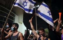 Two men wearing tank tops and face masks protest and wave blue and white Israeli flags in a big crowd