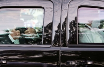 US President Donald Trump is shown through the glass of black SUV giving the thumbs up sign with both of his hands while wearing a face mask.