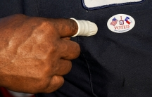 """A person wearing a finger sack points at an """"IVoted"""" sticker after casting ballot for the upcoming presidential election as early voting begins in Houston, Texas, Oct. 13, 2020."""