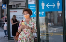 A woman wearing a face mask is seen in a bus stop next to an information sign asking people to keep social distance due to the outbreak of the coronavirusdisease (COVID-19), in Stockholm,Sweden, June 26, 2020.