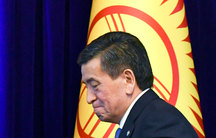 Sooronbay Jeenbekov is shown walking past the blue, yellow and red national flag.
