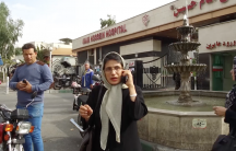 A woman stands on a street wearing a head covering and talking on the phone