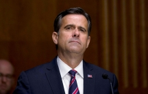 Director of National Intelligence John Ratcliffe is shown wearing a dark blue suit and striped tie with a US flag pin.