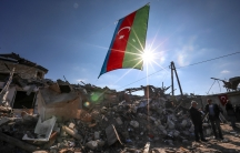 Azerbaijan's national flag is shown flying over destroyed houses with bright rays of sunlight backlighting it.