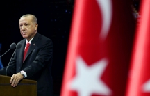 A man in a suit stands at a podium near red and white Turkish flag.