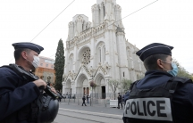 Police officers are shown standing guard across the street and holding large guns from the Notre Dame church in Nice.