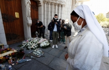 A nun prays in front of candles and flowers left in tribute to the victims of a deadly knife attack at the Notre Dame church in Nice, France, Oct.30, 2020.