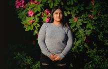 Una joven posa para una fotografia en frente de unas plantas.