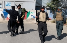 Several Afghan security officials are show wearing body armor and holding weapons.