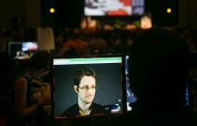 A small computer screen is shown in a dark room with Edward Snowden appearing in a close-up frame.