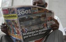 """A man reads the Diario 2001 newspaper that carries the Spanish headline: """"Agony is prolonged for the White House"""" at a newspaper stand in Caracas, Venezuela, Nov. 4, 2020, the day after US elections."""