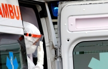 A person wearing white protective gear and gloves sits in the doorway of an ambulance.