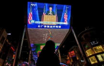 A woman sells balloons near a giant TV screen broadcasting news of US President-elect Joe Biden delivering his speech, at a shopping mall in Beijing, Nov. 8, 2020.