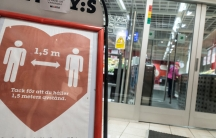 A sign reminding customers about social distancing is placed at the entrance to a grocery store in central Stockholm.