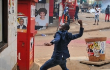 A person prepares to throw a rock during clashes between security forces and protesters supporting opposition presidential candidate Bobi Wine, in downtown Kampala, Uganda, Nov. 18, 2020.