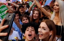 Several people surrounded by rainbow flags in a crowd cheer together in a parade and two people in front take a selfie