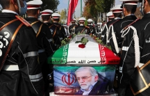 Rows of military personnel are shown on either side of a coffin that has an Iranian flag on top and a photo of Mohsen Fakhrizadeh on the side.