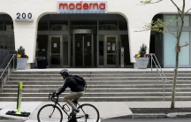 A bicyclist wearing a dark jacket and helmet is shown riding past the outside of drugmaker Moderna.