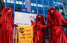 """Environmental activists hold a banner that reads: """"Because watching is not an option [anymore],"""" as they protest outside of a court during a hearing in a case environmentalist and human rights groups have brought againstRoyalDutchShellto force the ene"""