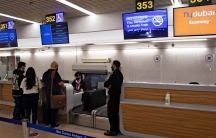 A group of three people are shown from behind standing at a ticketing agent desk at Ben Gurion airport.