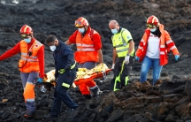 Rescue workers carry the body of a dead migrant after a boat with 35 migrants from the Maghreb region capsized atthe beach of Orzola, in theCanaryIsland of Lanzarote, Spain, Nov.25, 2020.