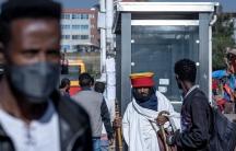 Passengers walk through a bus station in the capital Addis Ababa, Ethiopia, Nov. 6, 2020.