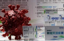 Samples of a COVID-19 vaccine produced by Sinopharm subsidiary CNBG are displayed near a 3D model of a coronavirus during a trade fair in Beijing on Sept. 6, 2020.