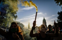 People are shown holding pipes letting off green smoke with the Argentine capital dome in the distance.