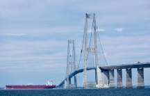 A large red oil tanker is shown in the distance passing underneath two tall bridge columns.