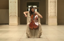 A woman playin cello appears in an empty museum hall.