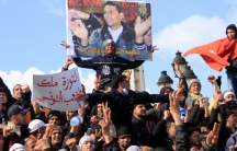 Tunisian protesters demonstrate beneath a poster of Mohamed Bouazizi near the prime minister's office in Tunis, Tunisia, Jan. 28, 2011.
