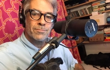Marco Werman is shown with a microphone and his dog Frankie sitting on his lap.