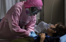 Dressed in protective gear to curb the spread of the new coronavirus, a medical worker massages a patient, at a military hospital set up to take care of COVID-19 patients.