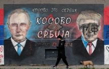 A woman with a dog passes by graffiti depicting the Russian President Vladimir Putin, left, and USPresident Donald Trump vandalized with paint in a suburb of Belgrade, Serbia, Nov. 3, 2020.