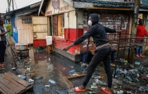 In this March 26, 2020, file photo, a boy wears a mask as a preventative measure against the spread of the coronavirus, as he navigates floodwaters mixed with garbage following heavy rains, in the Kibera area of Nairobi, Kenya.