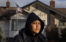 A woman is shown wearing a dark hooded sweatshirt and jacket with a home in the distance flying a tattered US flag.