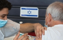 A health worker gives a shot in the arm to a person with silver hair in front of a blue and white Israeli flag.