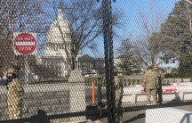 Members of the US National Guard stand inside anti-scaling fencing that surrounds the Capitol in Washington, Jan. 10, 2021.
